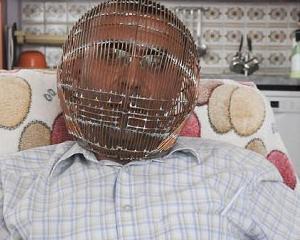 Un turc poarta o colivie pe cap, pentru a se lasa de fumat